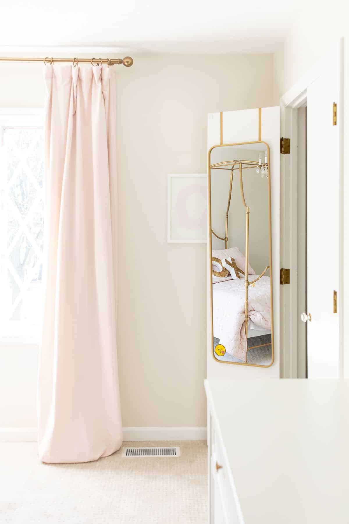A girl's bedroom with pink curtains, light carpet and white painted baseboards.
