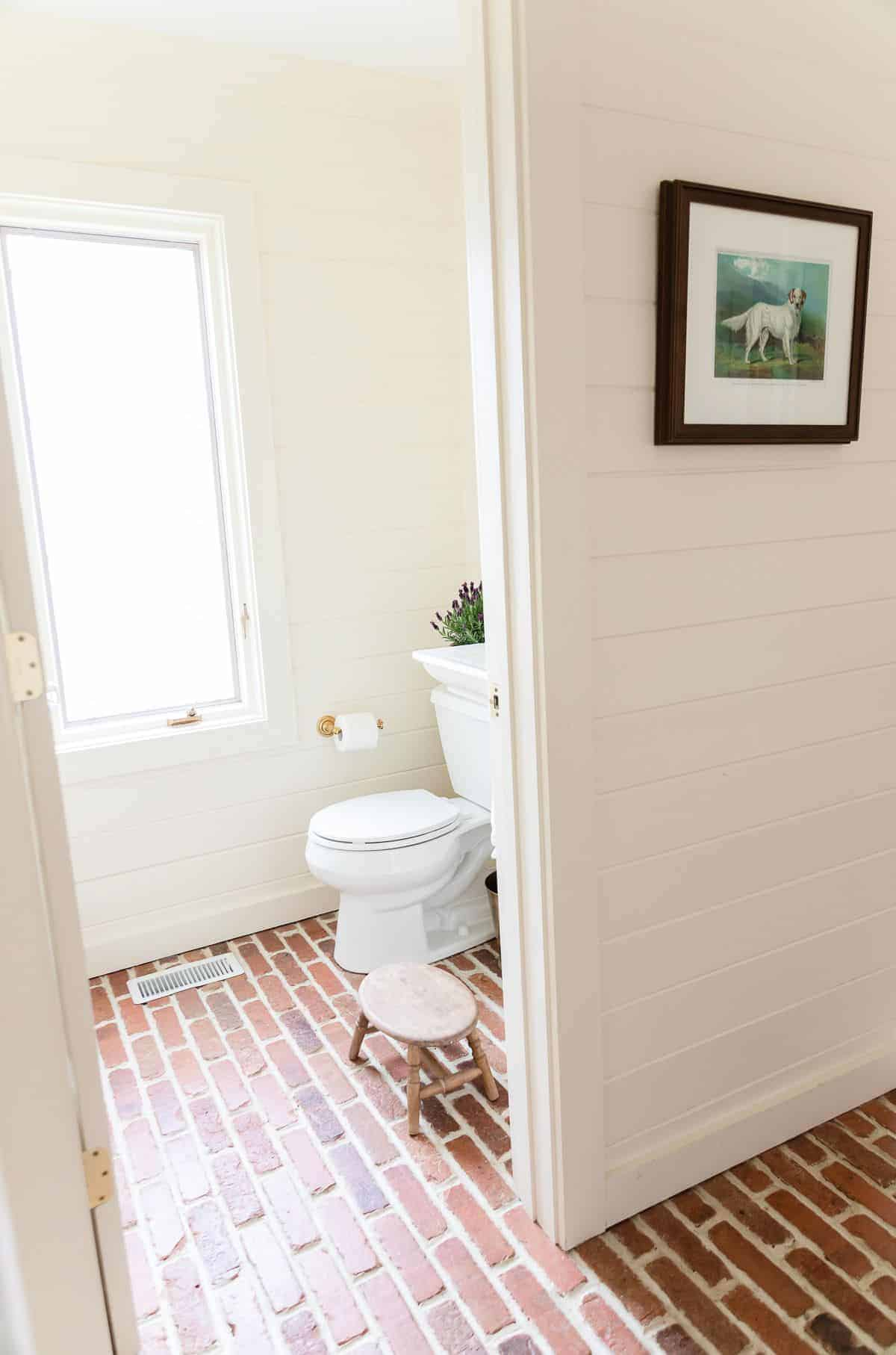 A white bathroom with white shiplap, white painted baseboards and brick floors,