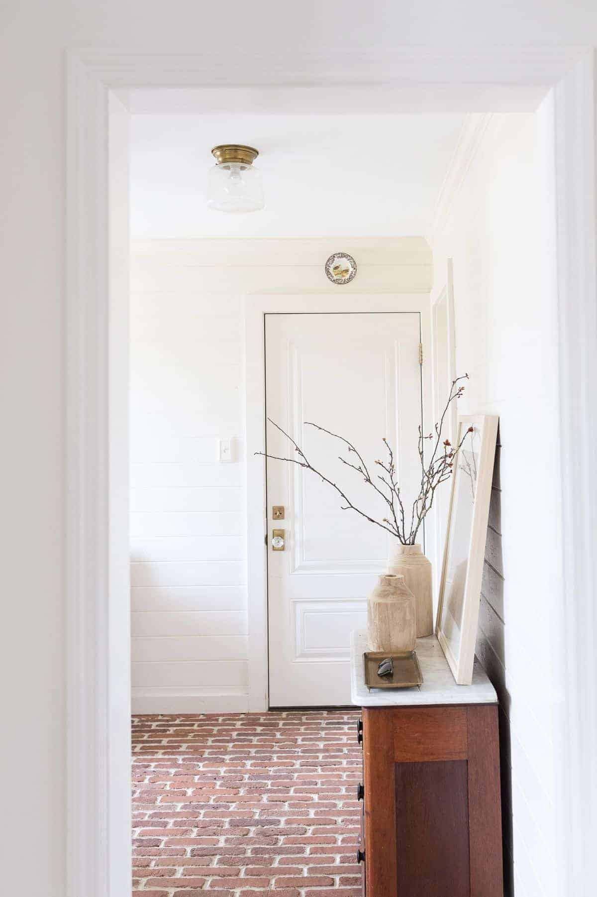 A white mudroom with brick floors.