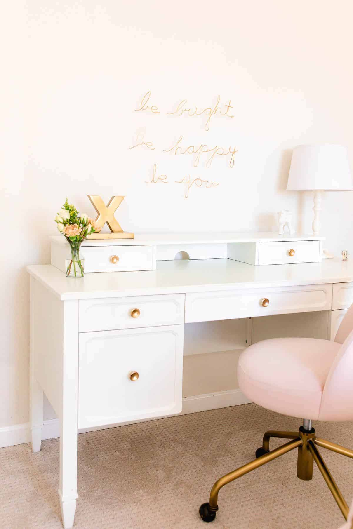 A white desk in a girl's bedroom with white walls and a pink chair.