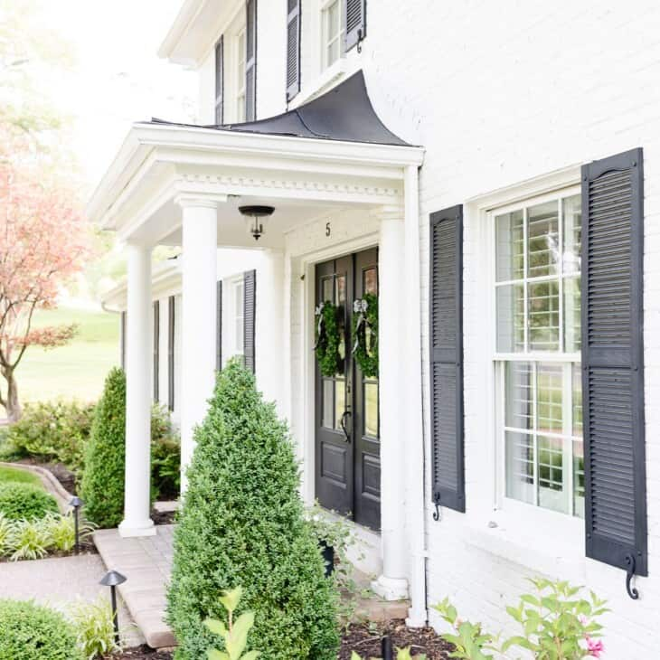 simply white benjamin moore exterior of a colonial home with black shutters.