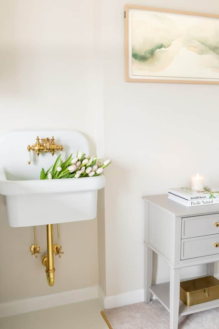 A wall sink filled with white tulips in a laundry room.