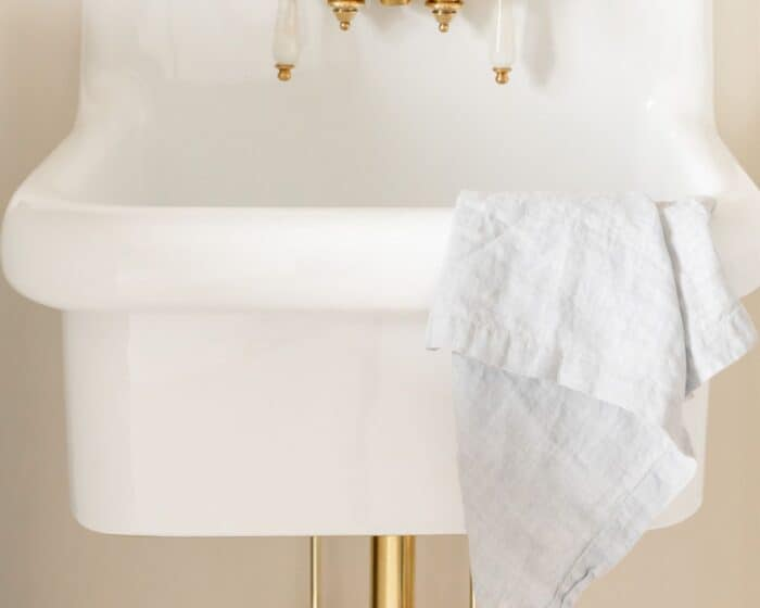 A white wall mount sink with brass hardware.