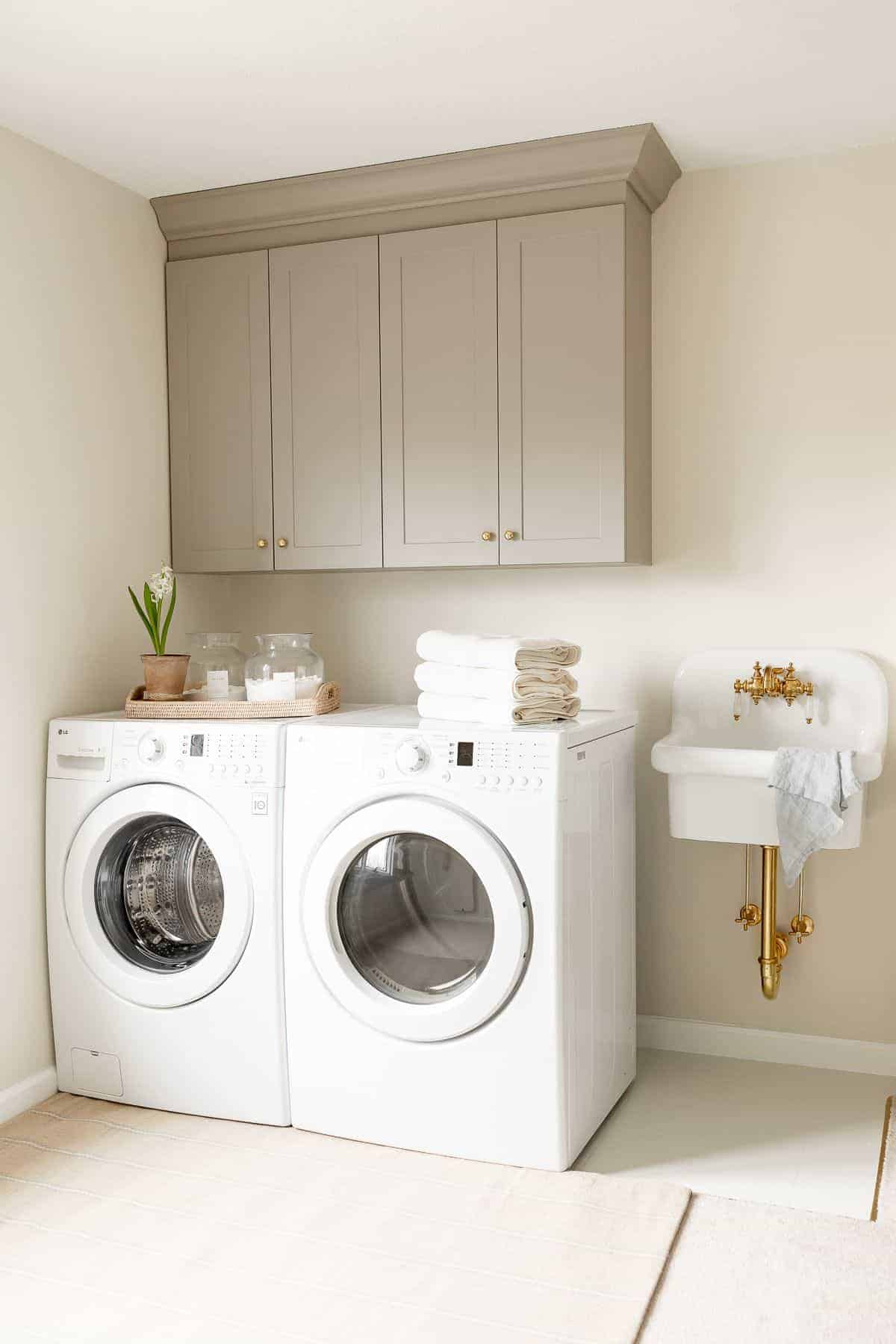 A laundry room with gray cabinets and a small wall sink.