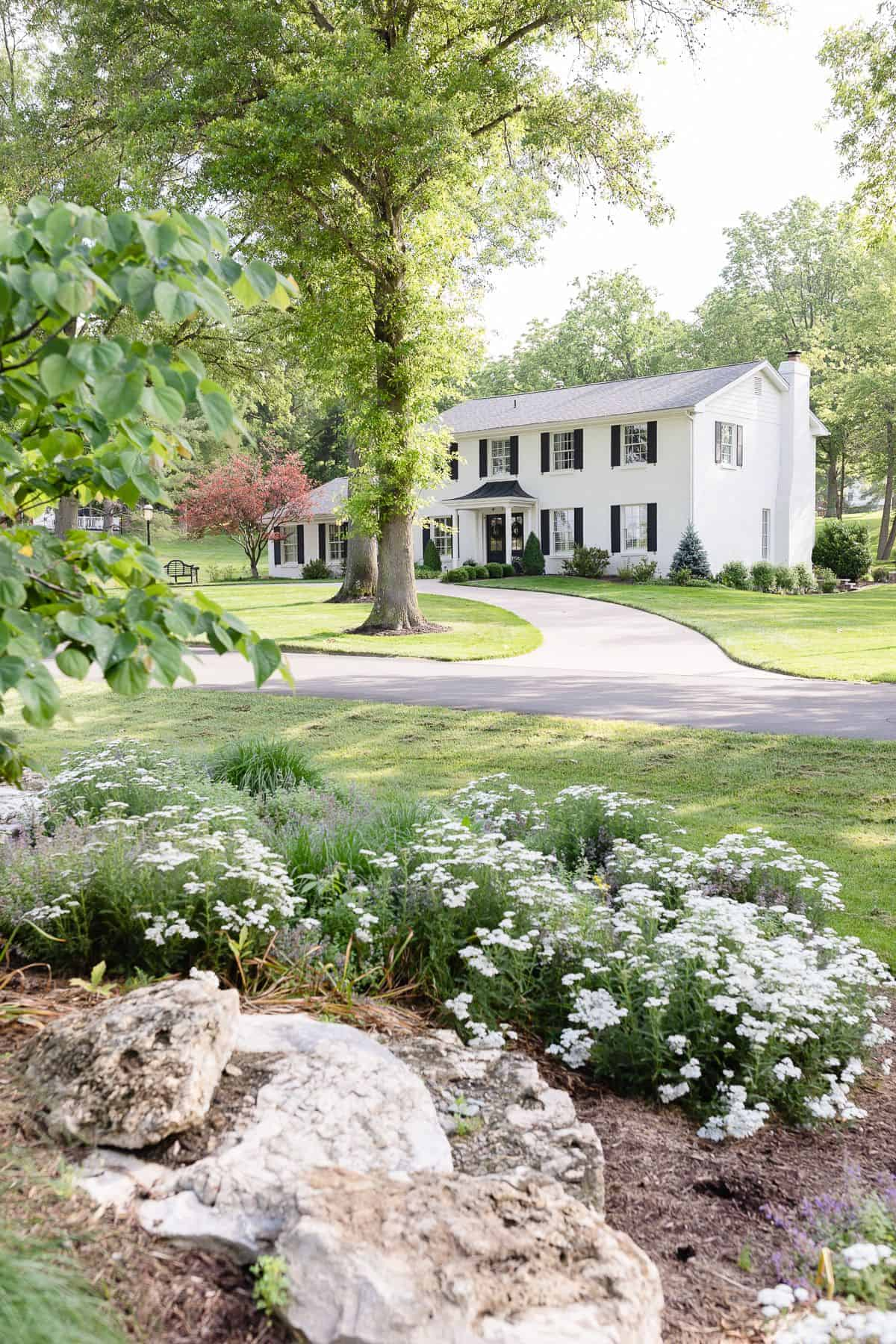 A white brick house sitting amongst green trees and flowers.