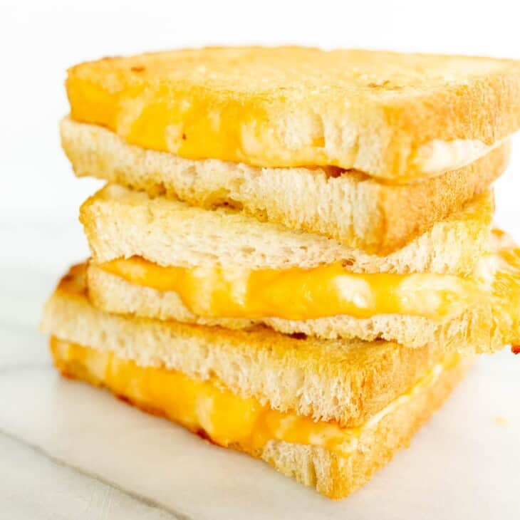 A stack of oven grilled cheese sandwiches, sliced on a white surface.