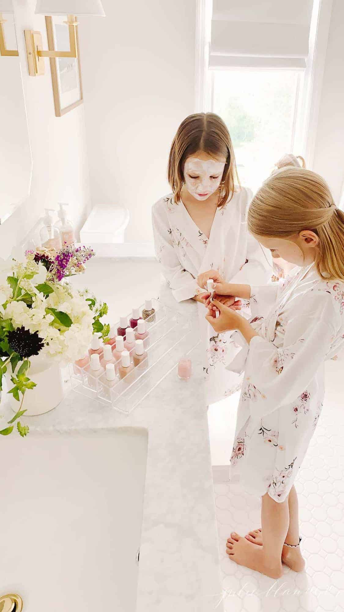 Two little girls in face masks in a white bathroom, painting nails.