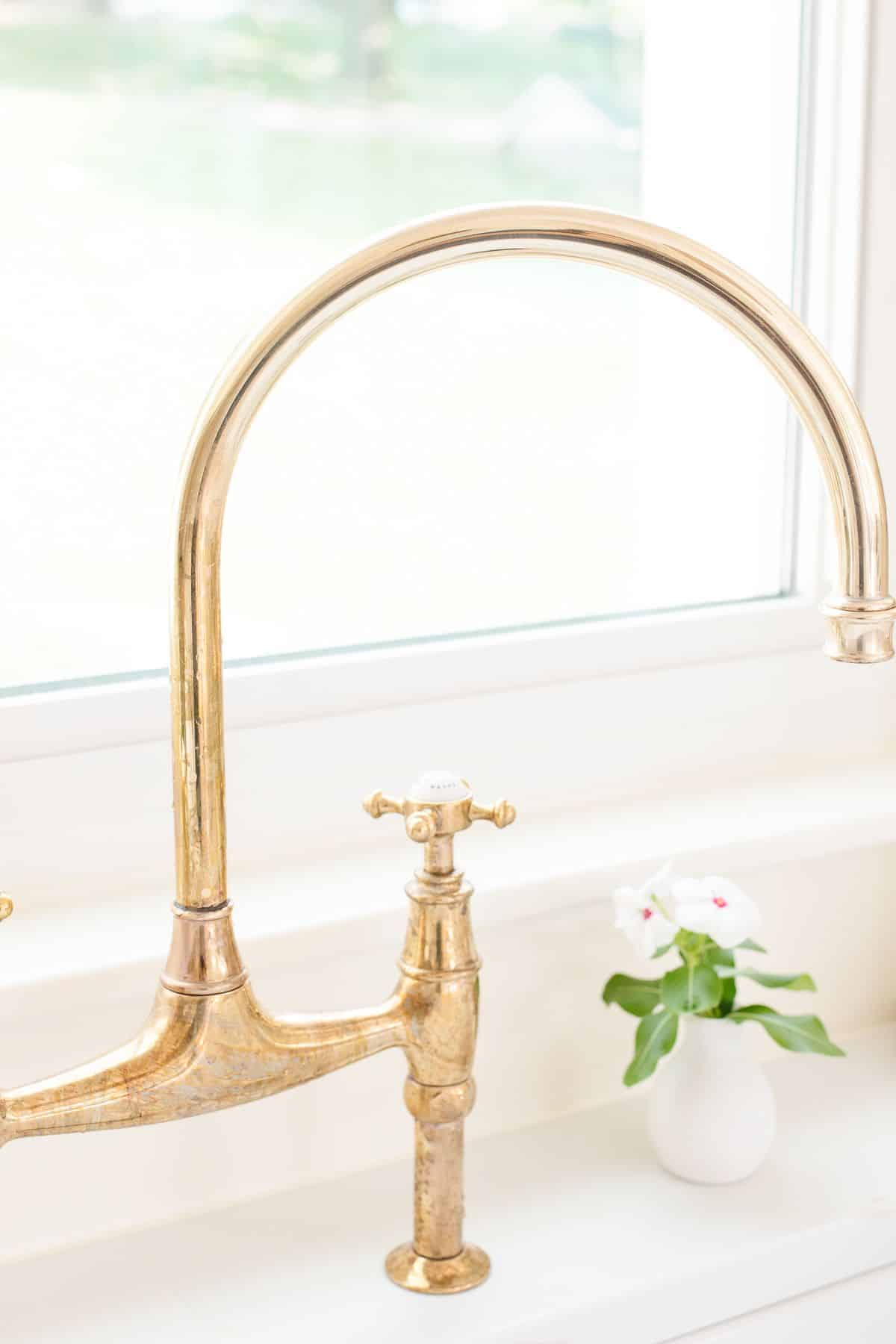 A brass kitchen faucet with some tarnish.