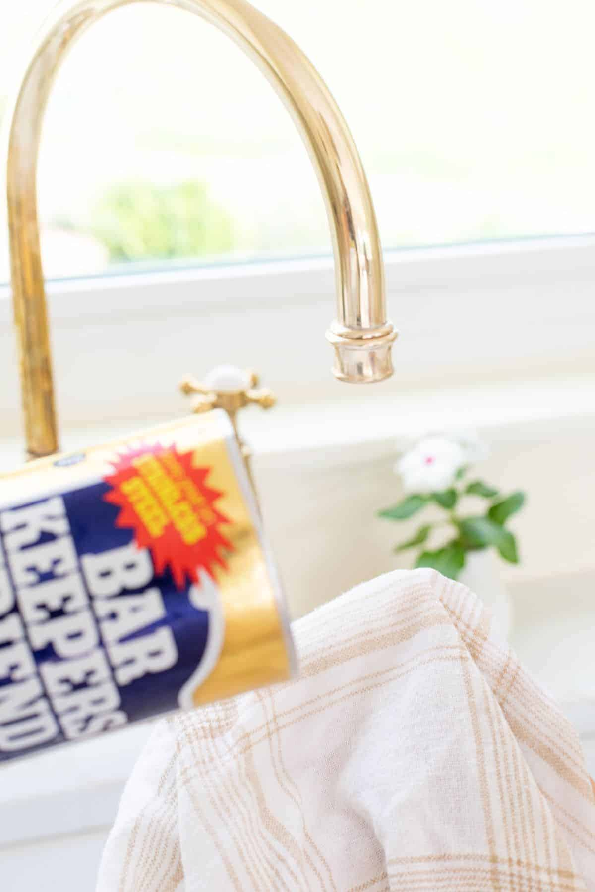 A tarnished brass faucet being scrubbed with a soft cloth and the best brass polish.