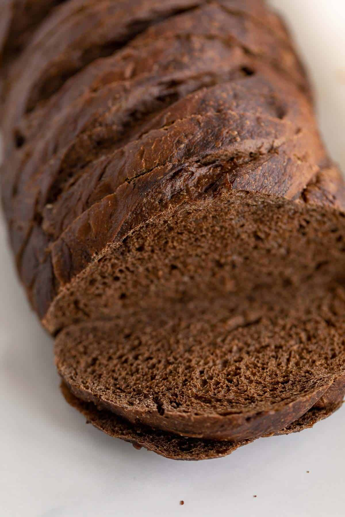 A loaf of dark rye bread, sliced on a marble countertop.