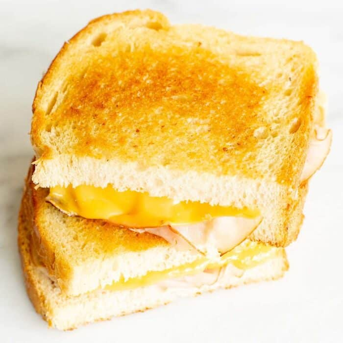 A grilled cheese sandwich with ham, sliced in half and stacked on a marble surface.