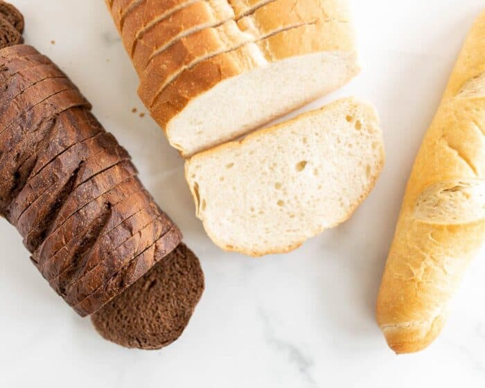 Three different loaves of bread on a marble surface, in a post about the best bread for grilled cheese.