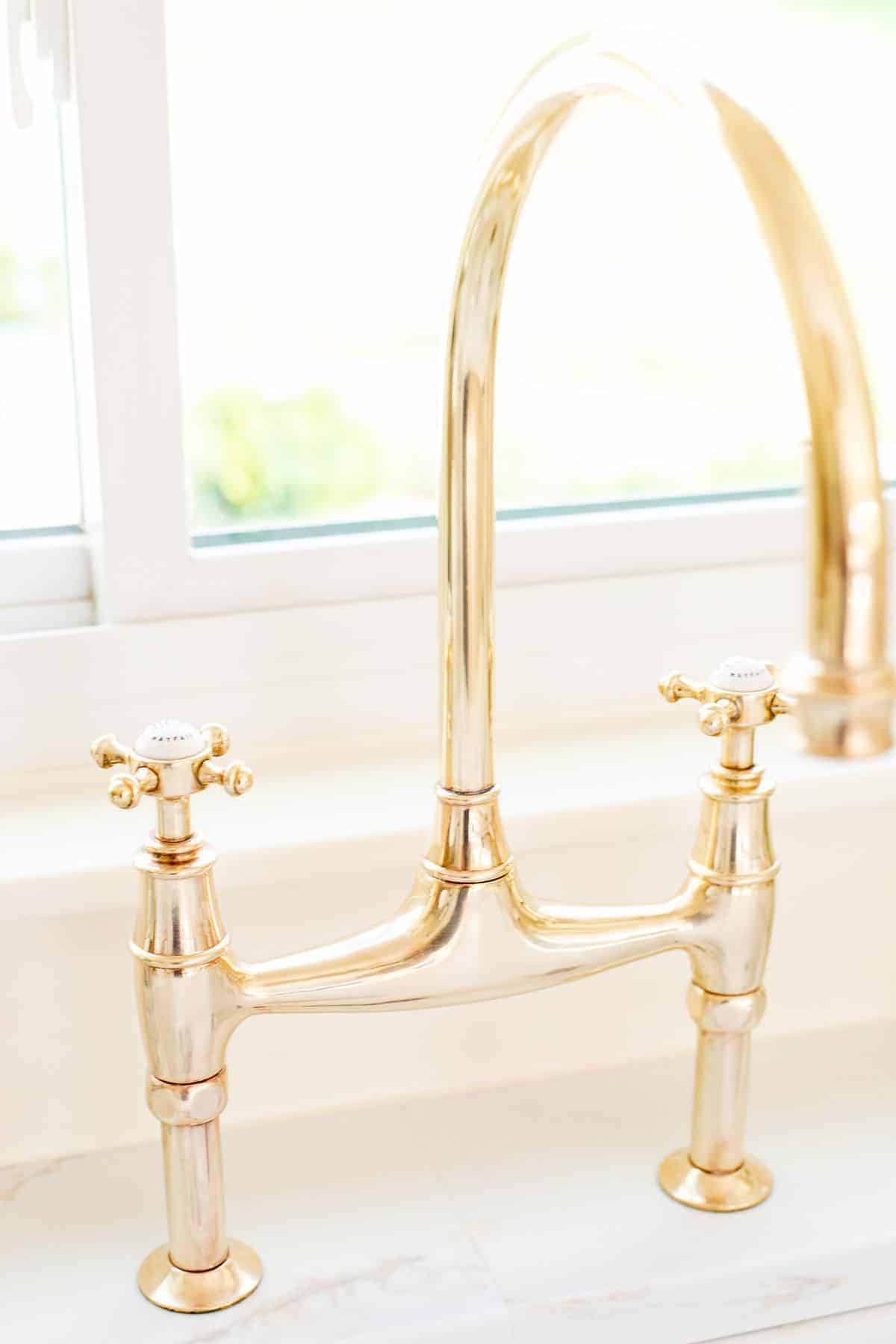 A brass bridge faucet that is shiny from brass polish.