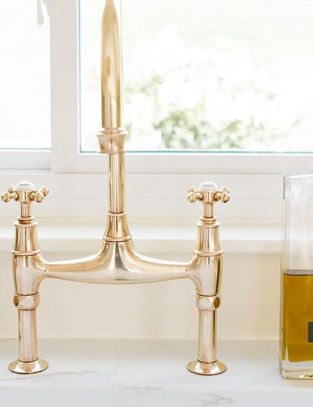 A brass bridge faucet that is shiny from brass polish, bottle of olive oil to the side.