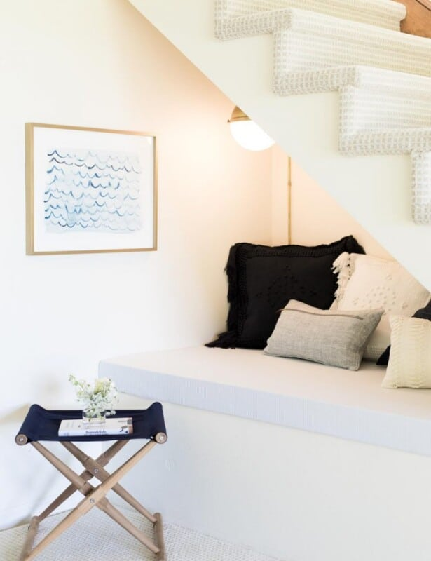 A nook under the stairs of a home with pillows, a wall sconce and art.