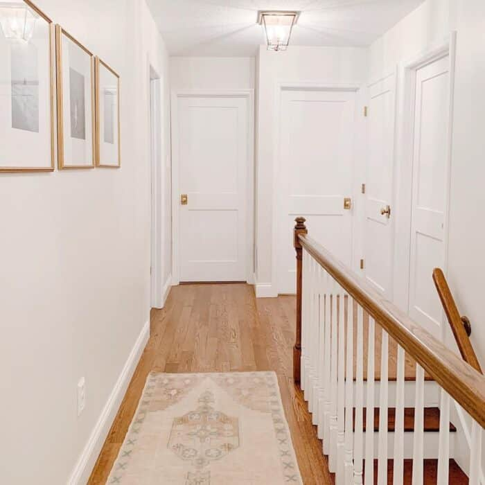 Soft white vs daylight in the overhead lanterns of a white home hallway.