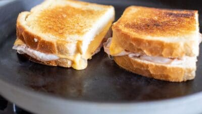 Two grilled ham and cheese sandwiches on a black cast iron pan.