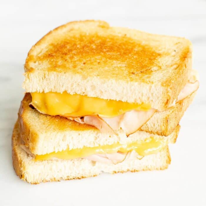 sliced grilled ham and cheese on white bread on a marble surface.