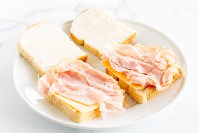 A white plate with sliced white bread topped with cheese and ham.