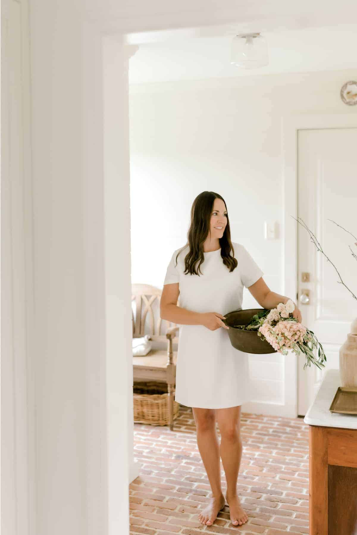 A woman in a white paneled mud room holding a basket of flowers.
