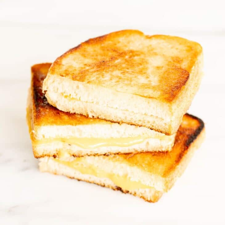 A stack of sliced grilled cheese with mayonnaise on a white marble surface.