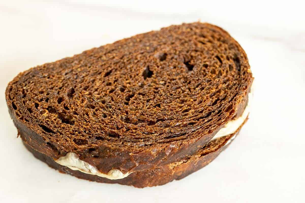 A grilled cheese on rye bread on a white surface.