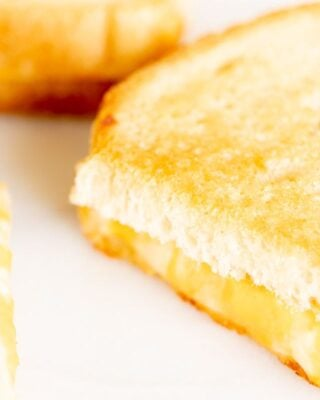 Oven grilled cheese sandwiches, sliced on a white surface.