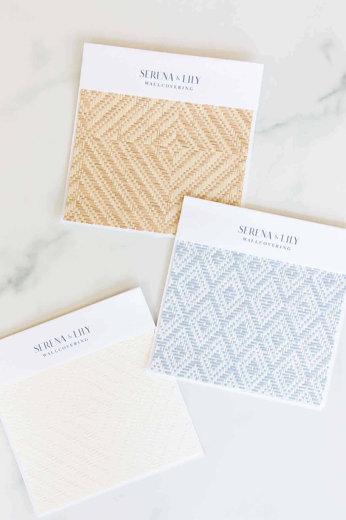 Wallpaper samples from Serena and Lily laid out on a marble surface.