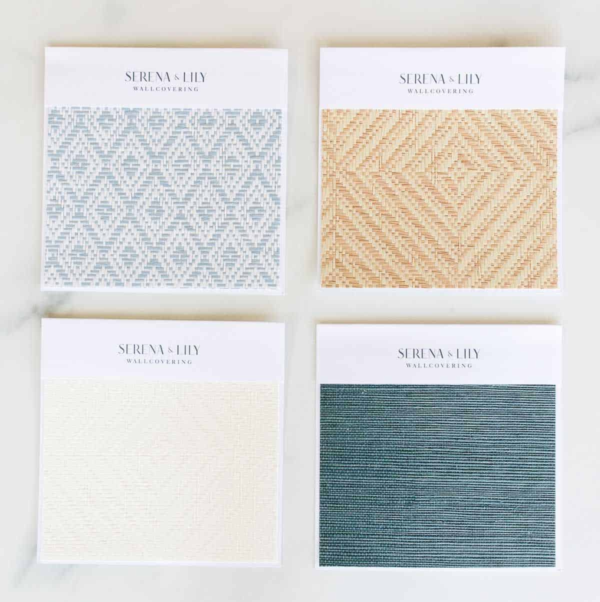 Four wallpaper samples from Serena and Lily laid out on a marble surface.