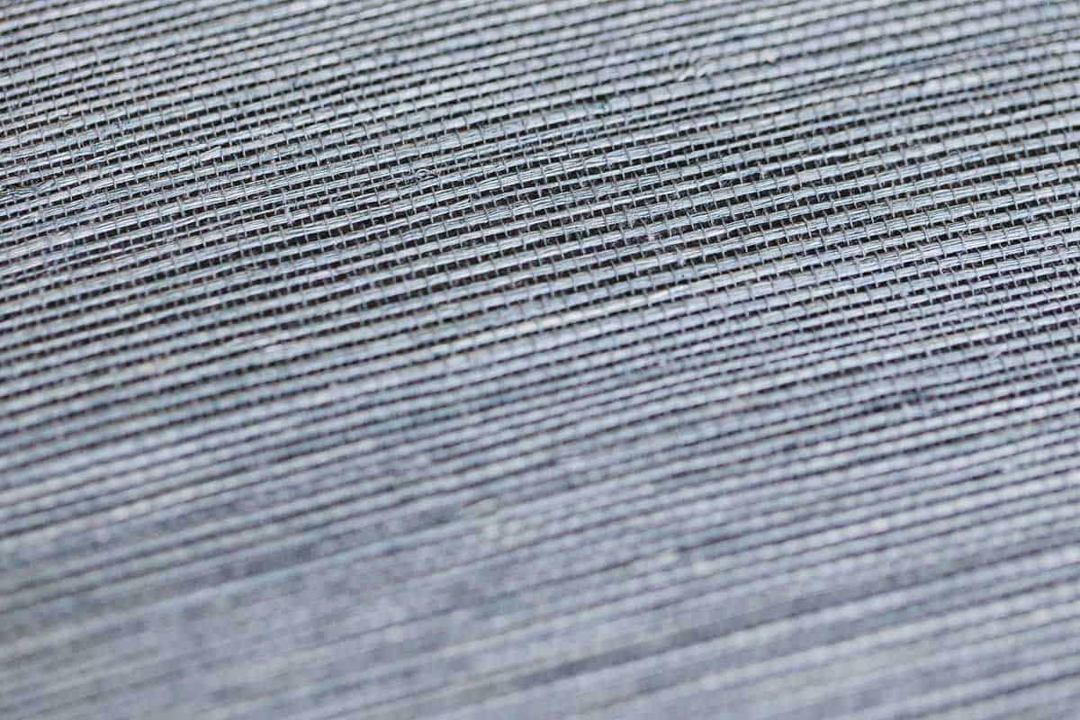 A close up of a navy blue grasscloth wallpaper