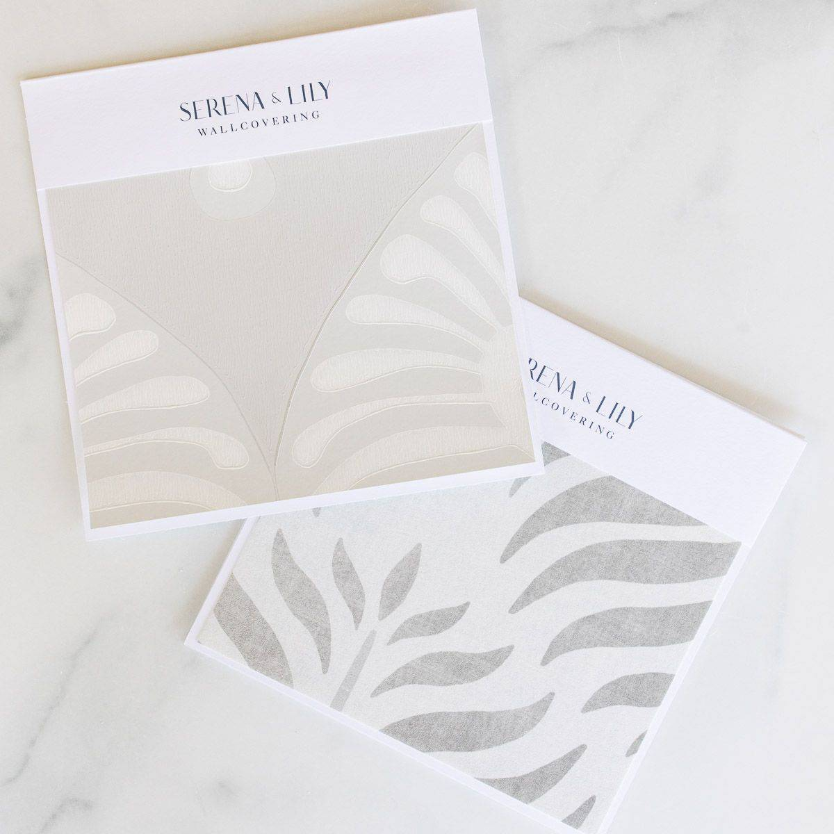 Two neutral patterned Serena and LIly wallpapers laid out on a white marble surface.
