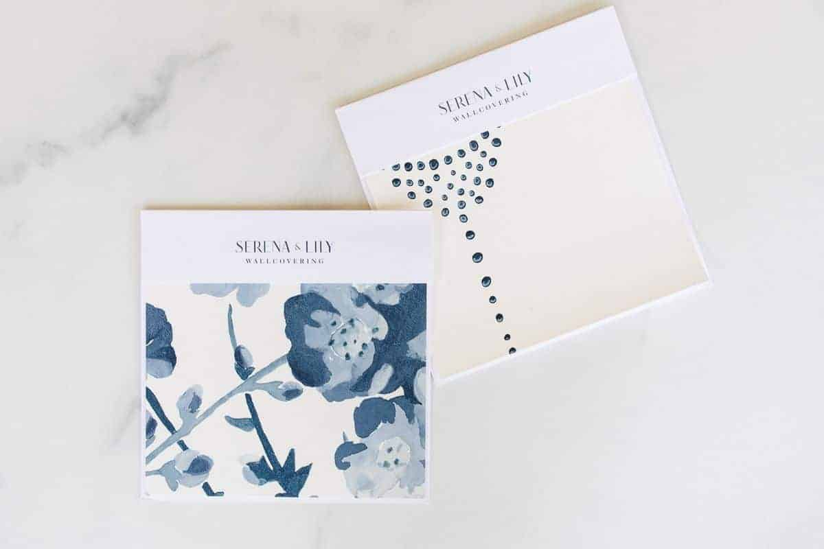 Two blue patterned Serena and LIly wallpapers laid out on a white marble surface.