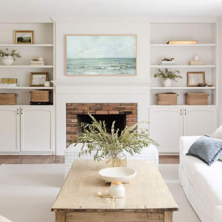 A small white living room with a large cream rug and white walls and furniture.