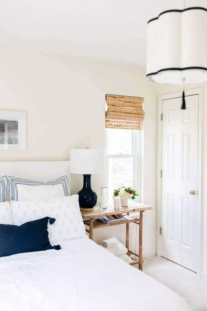 A small bedroom with a navy and white lamp and overhead pendant