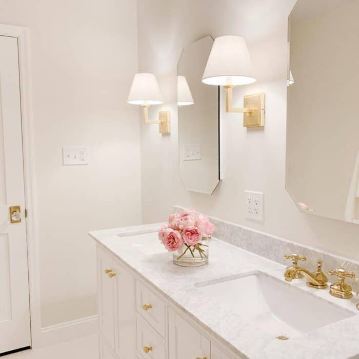 A bathroom with soft white light bulbs in the wall sconces.