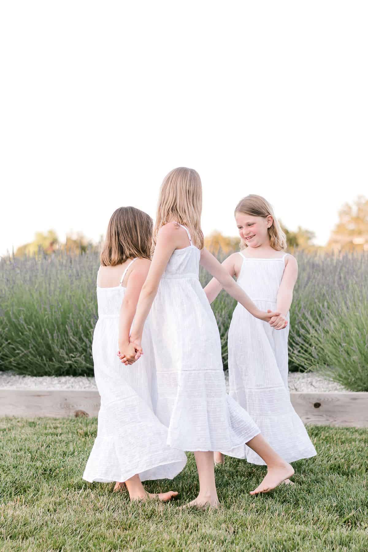 Three little girls in white dresses dancing in a field of english lavender.