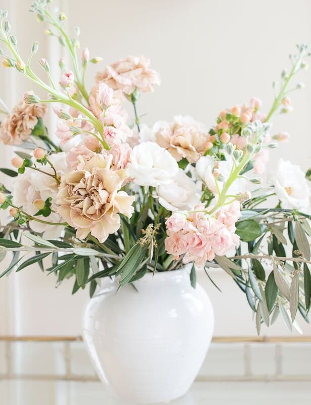 Antique carnations, stock and greenery in a white vase against a white background.