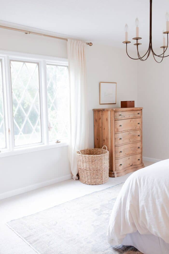 A white bedroom with a bedroom rug placement of a vintage rug under the bed.