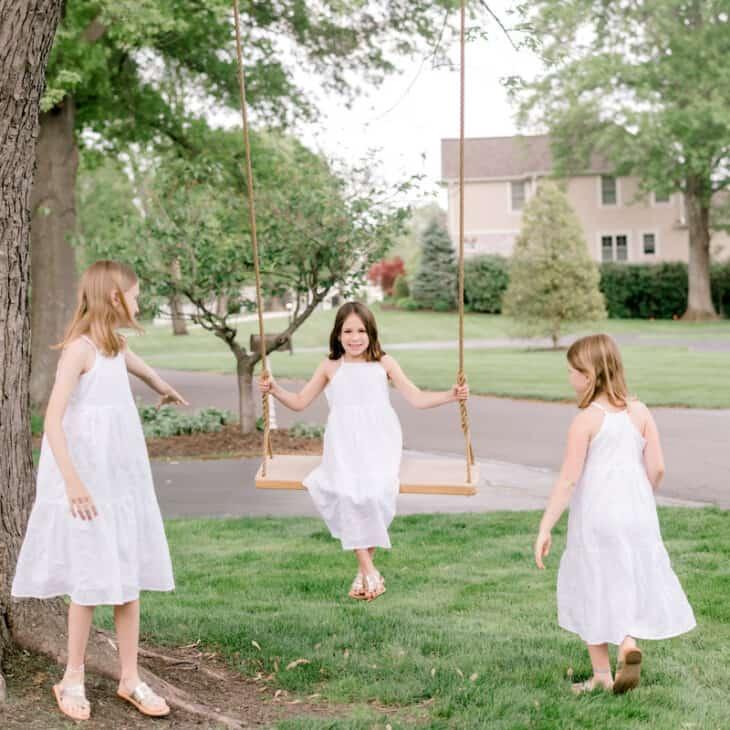 girls playing on wood tree swing