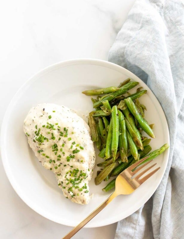 A Boursin chicken breast served with green beans on a white plate with a gold fork.