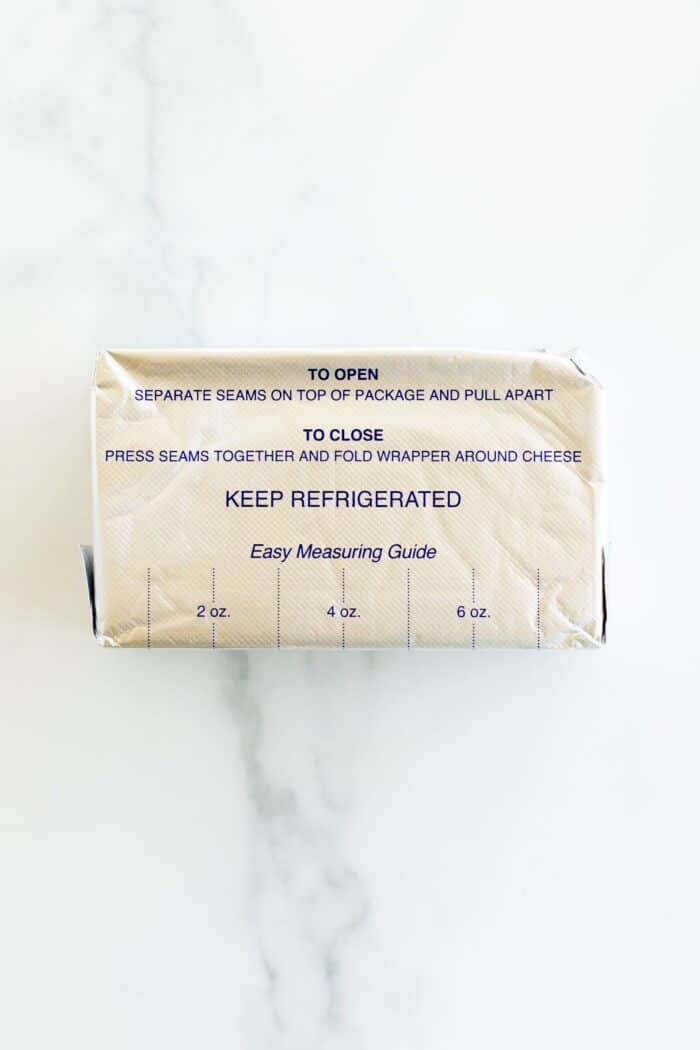 A block of cream cheese wrapped in foil packaging on a marble surface.