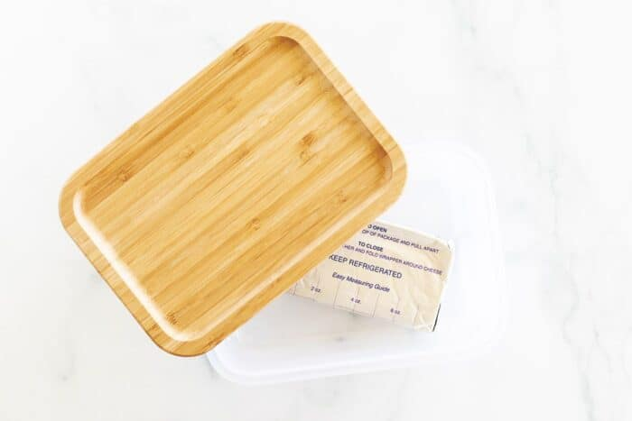 A block of frozen cream cheese inside a container with a bamboo lid.