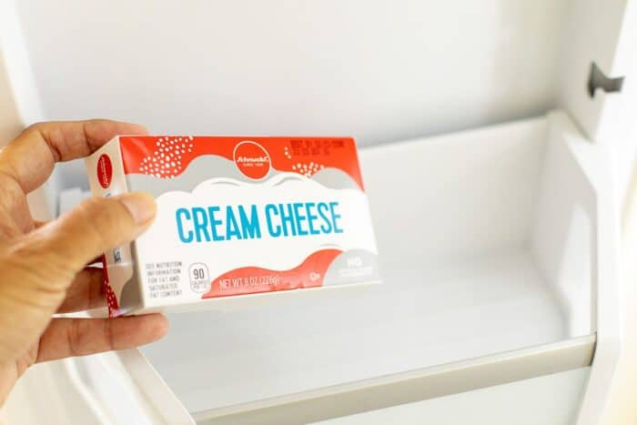 A hand placing a package of cream cheese in the freezer.