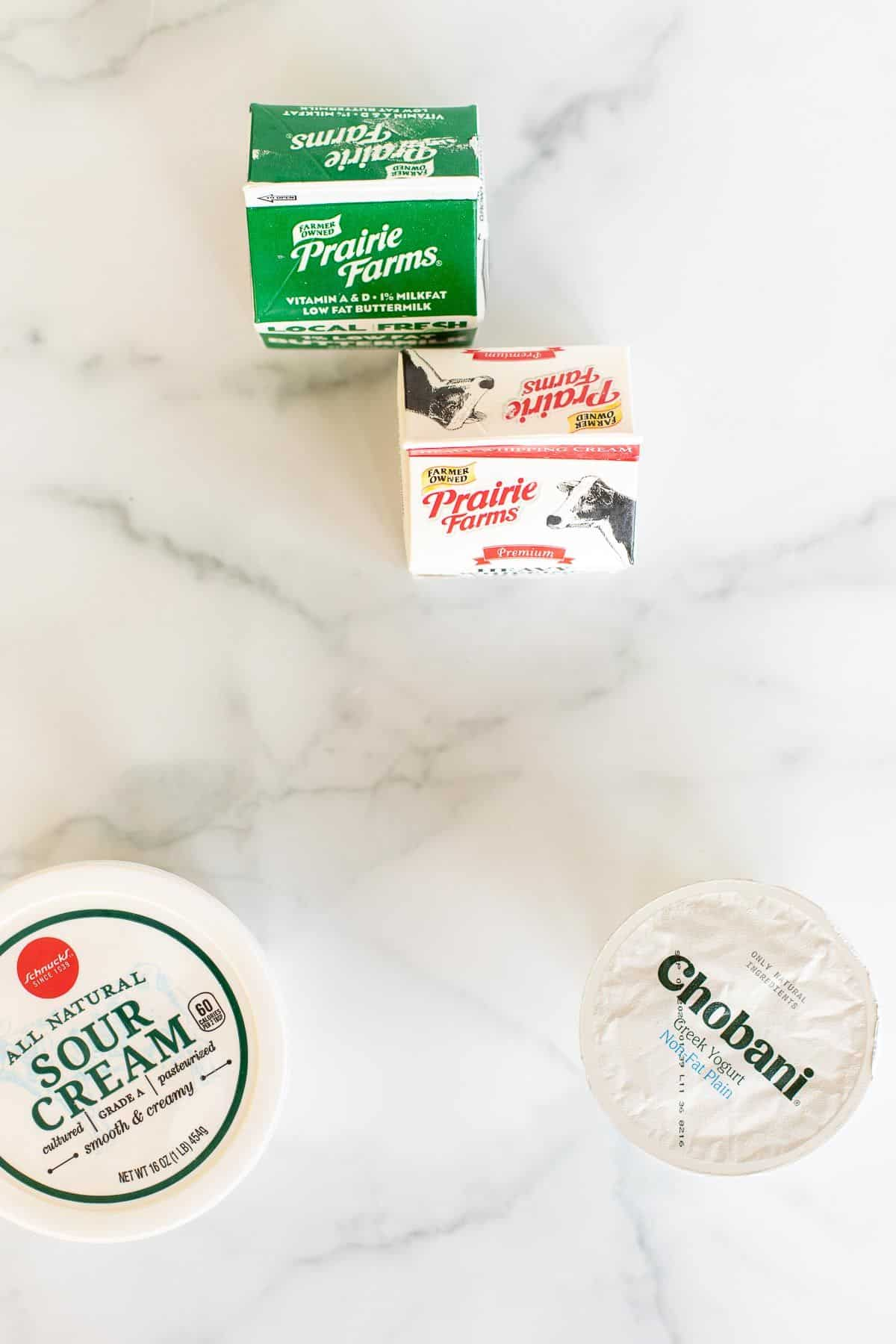 A small carton of buttermilk, a carton of whipping cream, a container of sour cream, and a small greek yogurt container all placed on a marble surface.