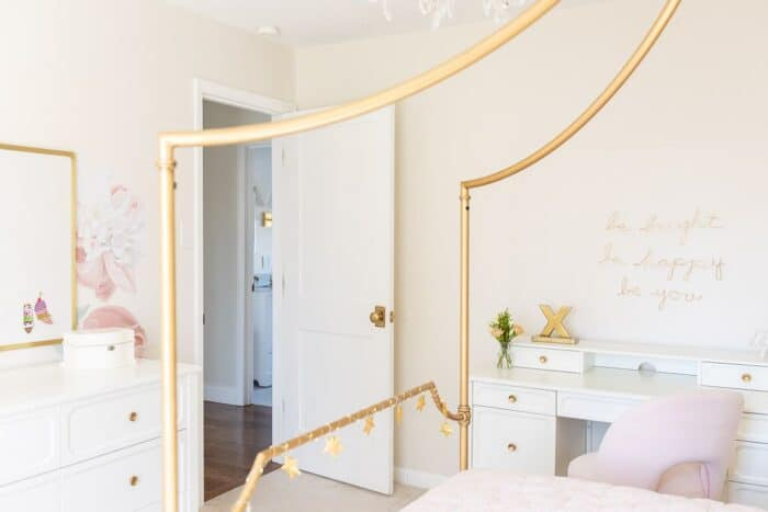 A teen girl's bedroom with a gold canopy bed and a white girls desk with pink chair