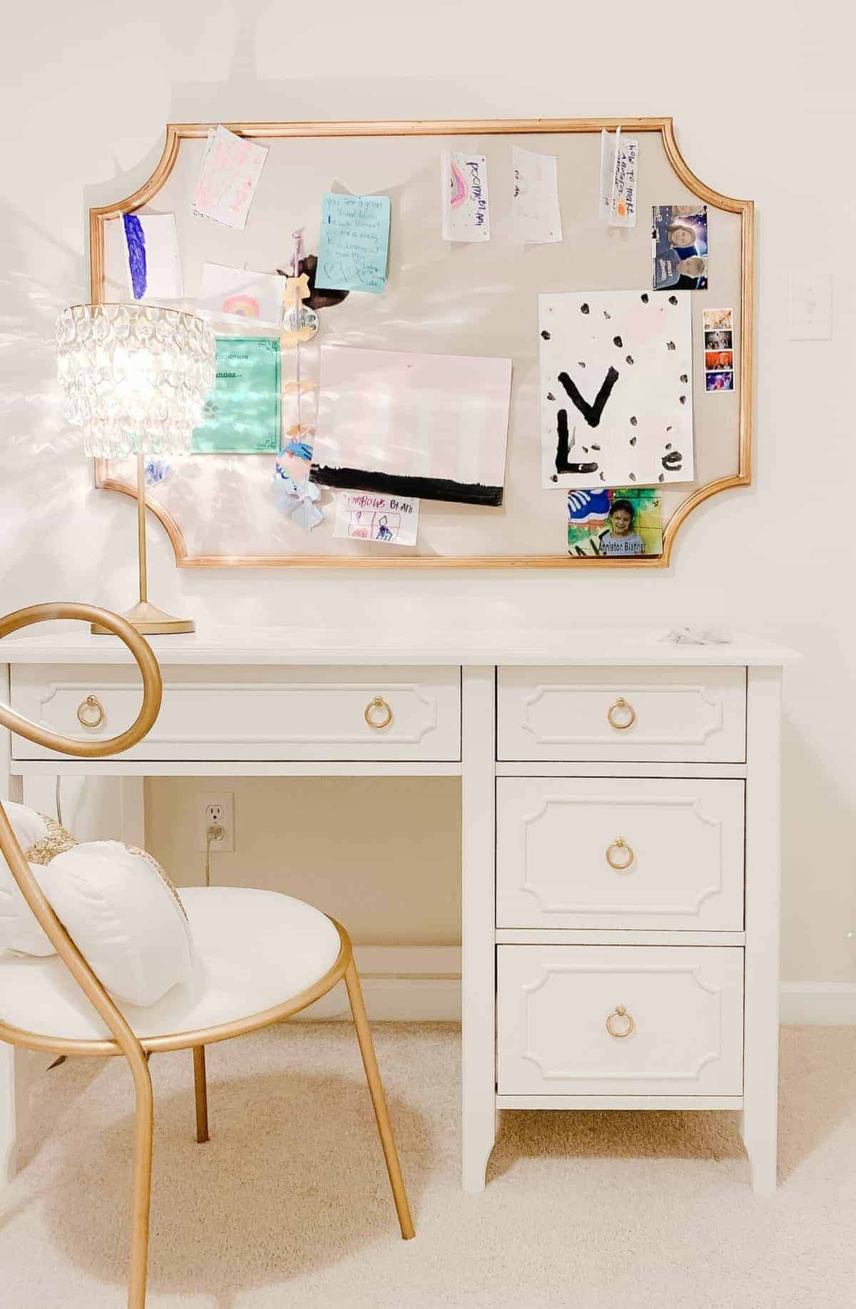 A white desk for teenagers in a girls bedroom, paired with a gold chair and pin board on the wall.
