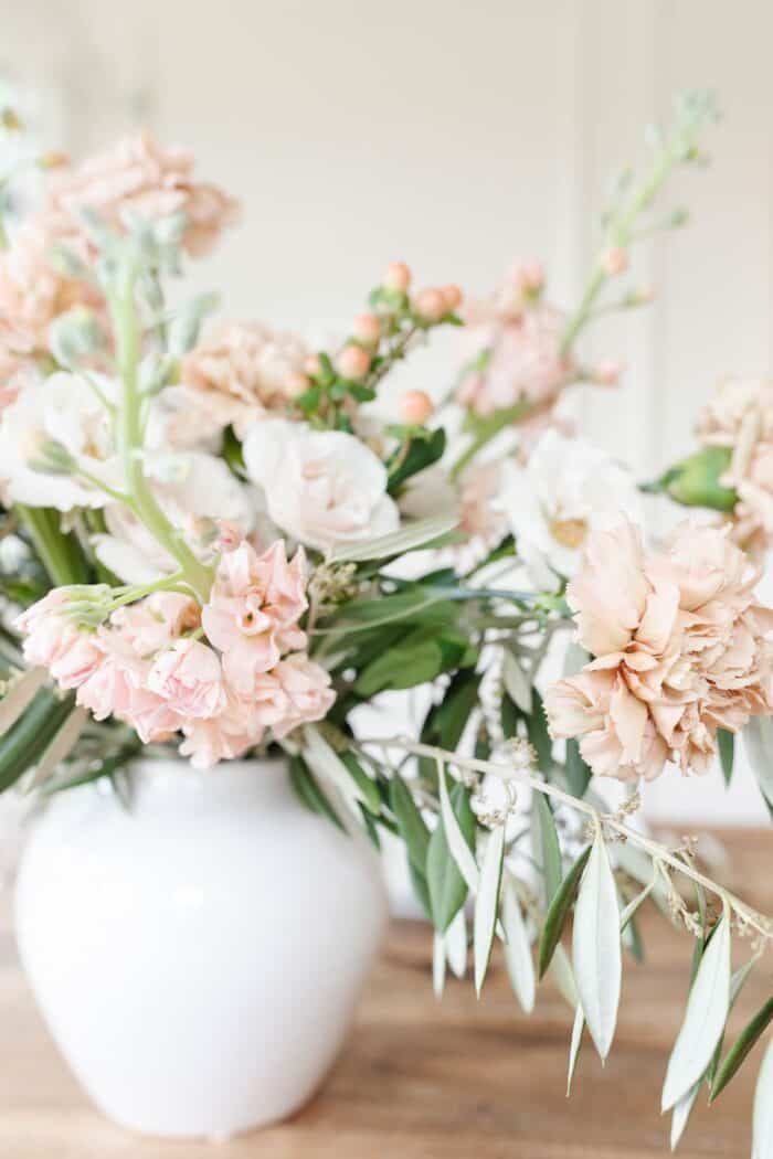 dianthus caryophyllus in a vase arrangement of antique and cream colors.