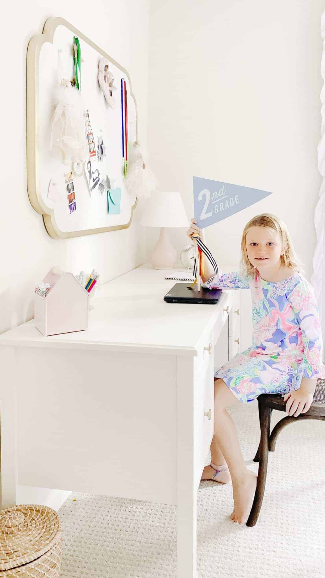 A young girl in a blue and pink dress at a white girls desk in a white bedroom.