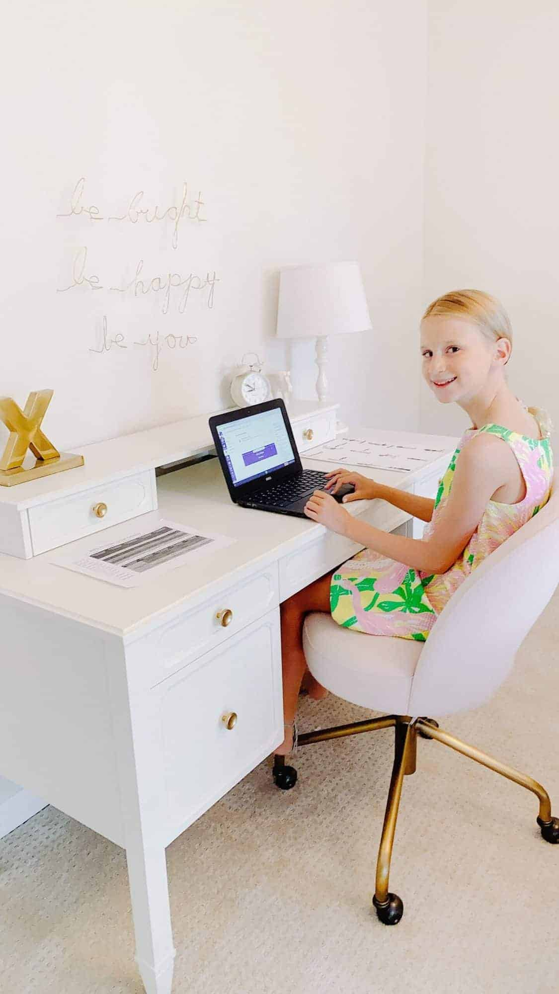 A young girl in a green and pink dress at a white girls desk in a white bedroom.