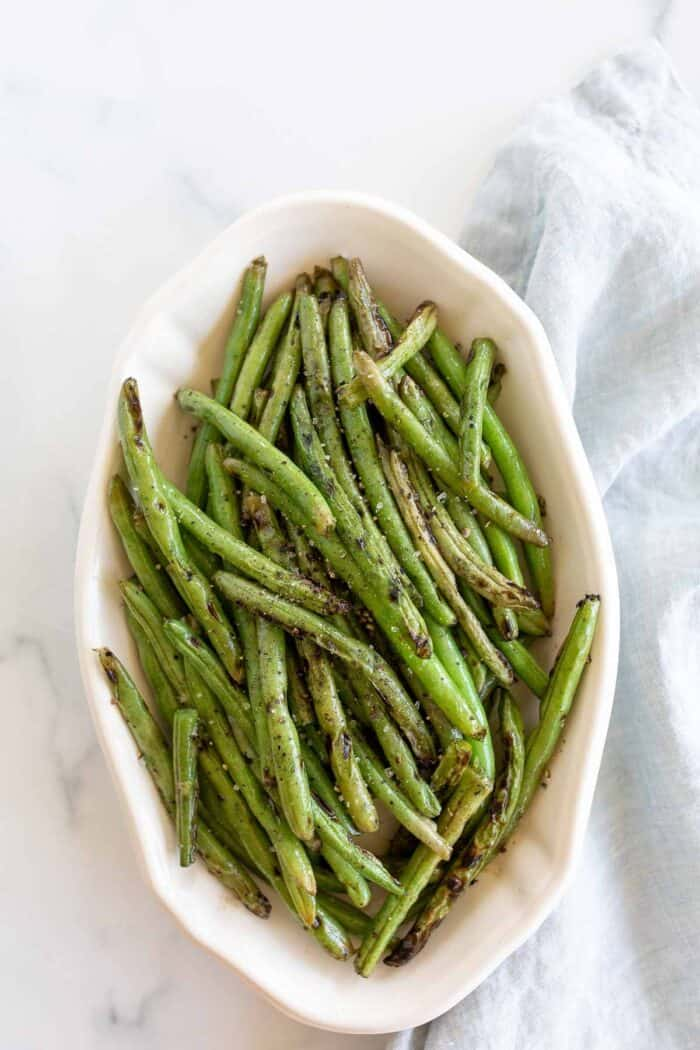 A white oval serving dish, filled with grilled green beans, blue linen towel to the side.